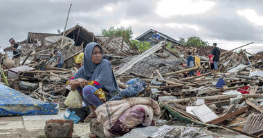 A tsunami survivor sits on a pice of debris as she salvages items from the location of her house in Sumur, Indonesia