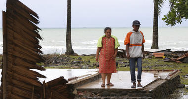 A tsunami survivor Kusmiati walks with her husband Aden at a destroyed villa caused by the tsunami in Carita, Indonesia,