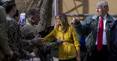 President Donald Trump and first lady Melania Trump greet members of the military as they arrive for a hangar rally at Al Asad Air Base, Iraq
