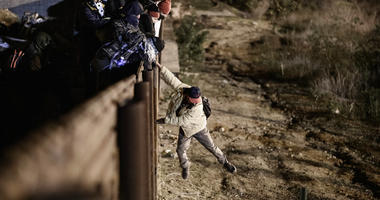 A migrant jumps the border fence to get into the U.S. side to San Diego, Calif., from Tijuana