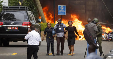 Security forces help civilians flee the scene as cars burn behind, at a hotel complex in Nairobi, Kenya Tuesday, Jan. 15, 2019