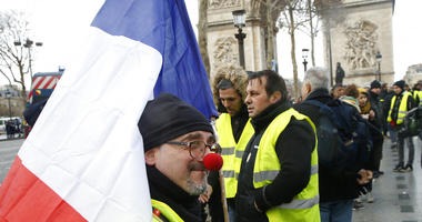 A Yellow vest demonstrator wearing a red nose gathers near the Arc de Triomphe before marching in Paris, Saturday, Jan. 26, 2019.