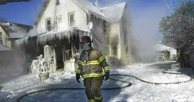 a firefighter walks past an ice-encrusted home after an early morning house fire in St. Paul, Minn.