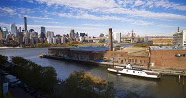 a rusting ferryboat is docked next to an aging industrial warehouse on Long Island City's Anable Basin in the Queens borough of New York