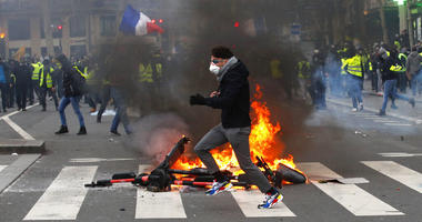A demonstrator runs by a fire during a yellow vest protest Saturday, Feb. 2, 2019 in Paris