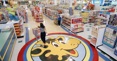 a woman pushes a shopping cart over a graphic of Toys R Us mascot Geoffrey the giraffe at the Toys R Us store