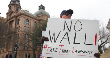 Carolyn Hursh, right, and Joey Daniel, carry a sign during a protest with others in downtown Fort Worth, Texas, Monday, Feb. 18, 2019. People gathered on the Presidents Day holiday to protest President Donald Trump's recent national emergency declaration