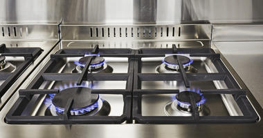 Burning blue flames of gas on cooktop under grills in a modern clean kitchen. Modern household appliance