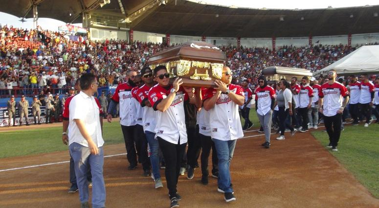 Players from the Cardenales de Lara baseball team carry the caskets of teammates and former major league players Luis Valbuena and Jose Castillo at a baseball stadium in Barquisimeto, Venezuela, Friday, Dec. 7, 2018