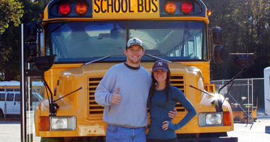 Jack Labosky, left, and Madi Hiatt pose after purchasing a school bus in Lynchburg, Va.