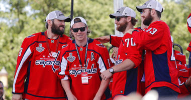 Washington Capitals' Alex Ovechkin (8), of Russia; Nicklas Backstrom (19), of Sweden; Braden Holtby (70); and Tom Wilson (43) greet each other on stage during the Stanley Cup victory celebration on the National Mall in Washington.