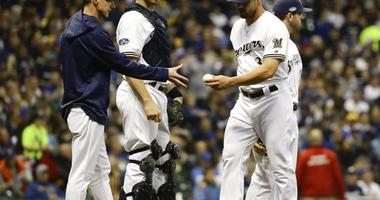 Milwaukee Brewers manager Craig Counsell takes relief pitcher Xavier Cedeno out of the game