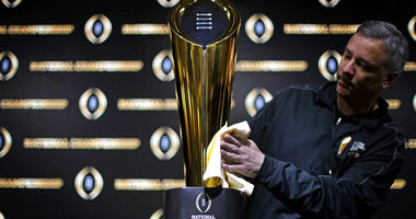 Charley Green buffs the NCAA college football championship trophy