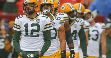 Green Bay Packers quarterback Aaron Rodgers (12) warms up with the team