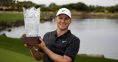 Adam Long holds the trophy on the 18th green after winning the Desert Classic golf tournament on the Stadium Course at PGA West on Sunday