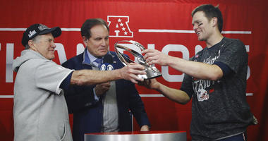 New England Patriots head coach Bill Belichick, left, hands off the championship trophy to quarterback Tom Brady after defeating the Kansas City Chiefs in the AFC Championship NFL football game