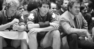 Boston Celtics coach Bill Fitch and players Rick Robey, center, and Larry Bird watch from the bench as their team loses to the Philadelphia 76ers 122-105 in an NBA basketball game Philadelphia.