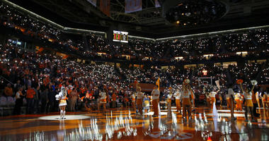 fans hold up their cell phones with the flashlight on as music plays before an NCAA college basketball game between Tennessee and Vanderbilt in Knoxville, Tenn.