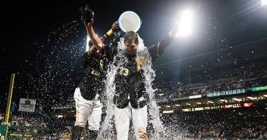 Pittsburgh Pirates first baseman David Freese (23) has water dumped on him by right fielder Gregory Polanco (25) after hitting a walk-off single to win the game against the New York Mets at PNC Park.