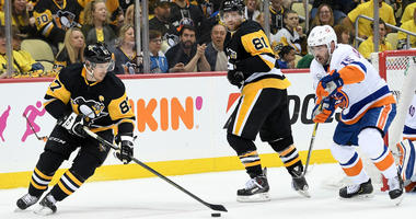 Sidney Crosby #87 of the Pittsburgh Penguins controls the puck against Cal Clutterbuck #15 of the New York Islanders