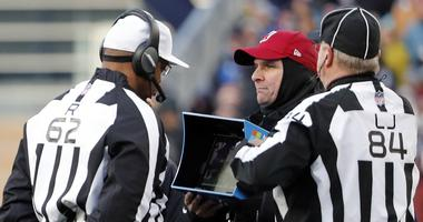 NFL referees wait for a replay during game