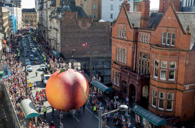 Members of the public gather to watch a giant peach as it is moved through the centre of Cardiff as part of a street performance to mark the start of City of the Unexpected, a celebration of the author Roald Dahl, on September 17, 2016 in Cardiff, Wales.