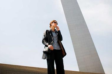 woman on phone in front of st. louis arch