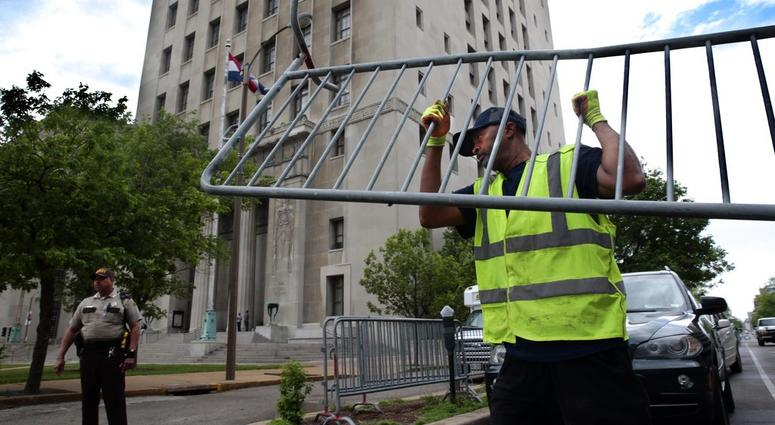 Members of the St. Louis streets department unload barricades on the side of the Civil Courts building in St. Louis, Mo., on Wednesday, May 9, 2018, in advance of Thursday's start of jury selection in the trial of Missouri Gov. Eric Greitens