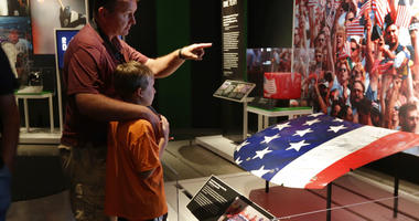 """Visitors to the National September 11 Memorial & Museum view the """"Comeback Season: Sports After 9/11"""" exhibit."""