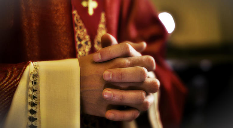 A close-up picture of a priest with hands clasped