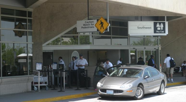 People unloading bags curbside at KCI
