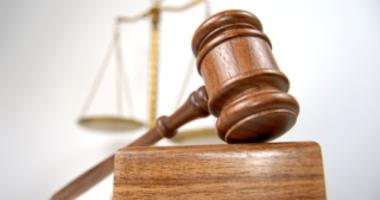 A gavel is shown in the foreground with the scales of justice behind