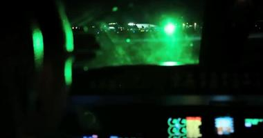 A green laser shines into the cockpit of an aircraft, potentially blinding the pilot