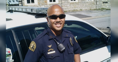 Officer Wagstaff smiles for a photo next to his police cruiser
