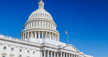 A crisp American flag flys on the US Capitol building