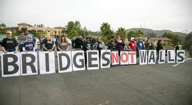 Hundreds of protesters gathers outside Our Lady of Mount Carmel Catholic Church to protest during President Trump's visit to see border wall prototypes.