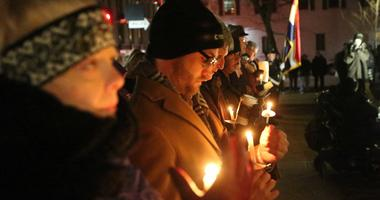 Attendees to a candlelight vigil for six that were killed during a City Council meeting in City Hall ten years ago, try to keep their flames going in Kirkwood, Missouri on February 7, 2018.