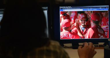 Woman using Facebook to watch St. Louis Cardinals baseball game.