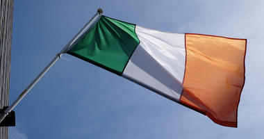 Irish flag fluttering in a wind against blue sky