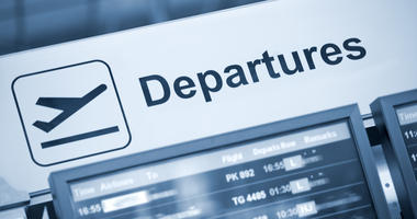 Close up view of airport departures sign blue toned