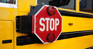Side view of a school bus and its the stop signal.