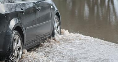 Car forcing a way through a flood on the River Ritec near Tenby, Pembrokeshire, UK