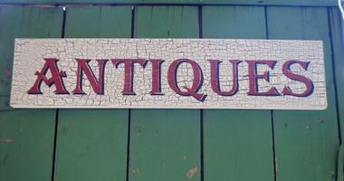 Maroon Red Antiques sign on wood. Spells out Antique, with turquoise wood background.