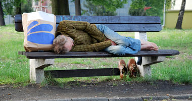 Old homeless man sleeping on bench