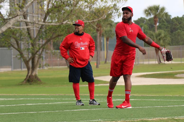 Outfielder Marcell Ozuna works with coach Jose Oquendo on a throwing drill.