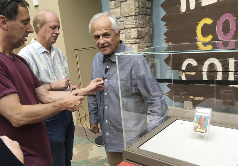 Marshall Fogell stands next to the display case containing one of the rarest baseball cards circulating, a 1952 Topps Mickey Mantle, that he owns