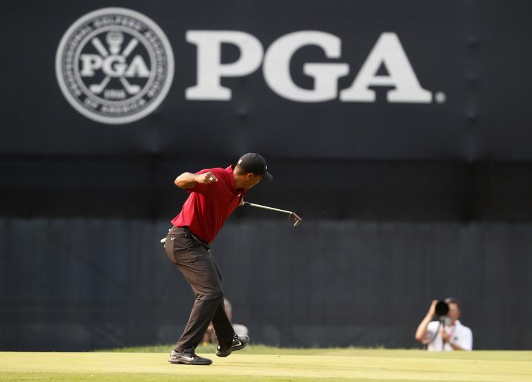 Tiger Woods celebrates his birdie putt on the 18th green
