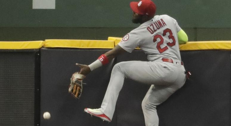 St. Louis Cardinals' Marcell Ozuna can't catch a double hit by Milwaukee Brewers' Jesus Aguilar during the first inning.