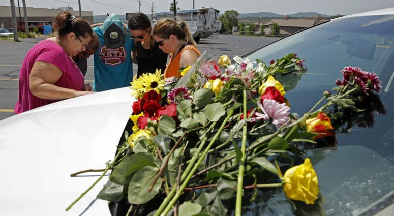 People pray next to a car believed to belong to a victim of a last night's duck boat accident, Friday, July 20, 2018 in Branson, Mo.
