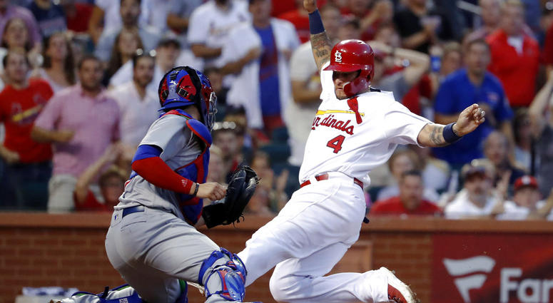 St. Louis Cardinals' Yadier Molina (4) scores past Chicago Cubs catcher Victor Caratini during the third inning of a baseball game Friday, July 27, 2018, in St. Louis.